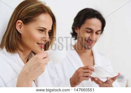 Enjoying every minute. Close up of adult beautiful woman in white robe holding cup with drink with her husband in background