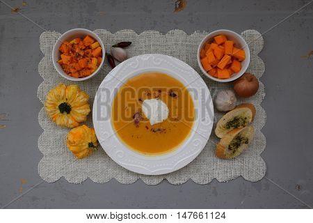 Pumpkin soup in white plate on wooden tabl