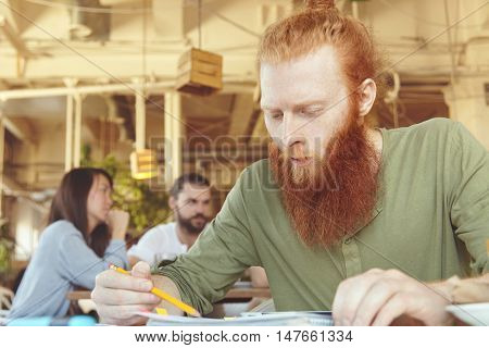 Headshot Of Redhead Student Working On His Graduation Project On Touch Pad Pc, Sitting At Coffee Sho