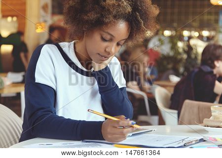 Close-up Portrait Of Tender African Female Freelancer At Cafeteria Working On Her Tablet, Writing Ou