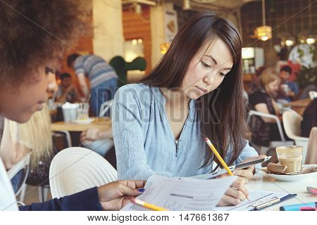 Two Female Students Doing Home Task At Cafe, Having Coffee. Asian Girl Holding Touch Pad, Writing Ou