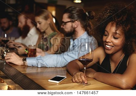 New Year Party And Celebration Concept. Friends Of Diverse Ethnicities At Nightclub Sitting At Bar C