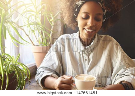 Attractive African Student Girl With Cute Shy Smile And Closed Eyes, Wearing Oversize Shirt, Having