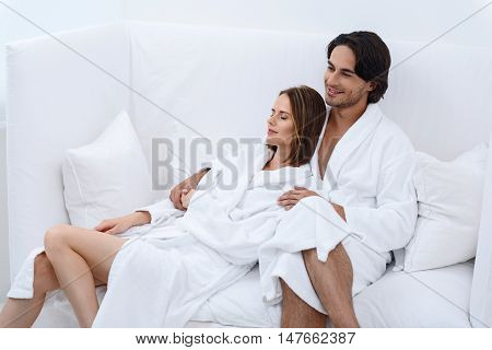 Traditional spa day. Beautiful young couple relaxing in spa salon, sitting on white couch in white terry robes