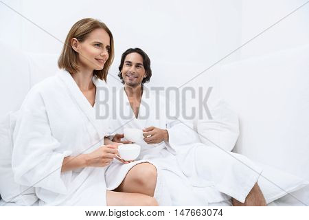 Ready to be pampered. Beautiful woman spending time with smiling man and drinking tea while sitting on white couch in spa center