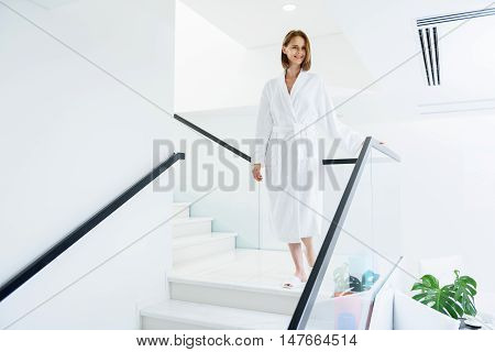 This spa has everything. Beautiful adult woman walking down stairs in spa center, holding her hand on railing