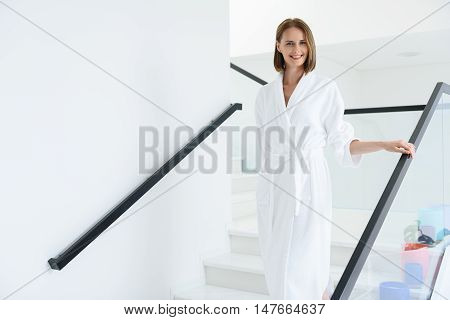 This is my holiday style. Beautiful young woman in white robe walking on stairs of spa center, smiling and looking at camera