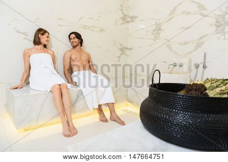 Relaxation at its best. Beautiful smiling couple looking each other while sitting in sauna and relaxing