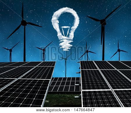 Solar panels with wind turbines and lightbulbs from clouds in night . The concept of sustainable resources.