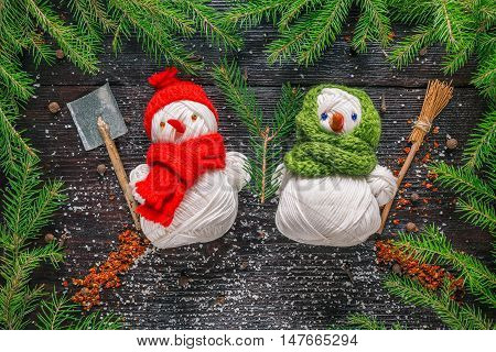 Pair of handmade yarn snowmen in the frame of evergreen branches and spices on the dark wood surface