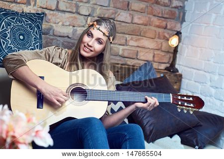 Happy young blonde woman singing and playing the guitar at home in wreath.