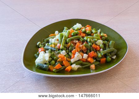 Boiled vegetables on the plate on the table.