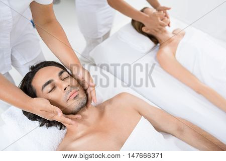 Taking some time for ourselves. Top view of man lying on mat and receiving head massage by two female hands with his girlfriend in background