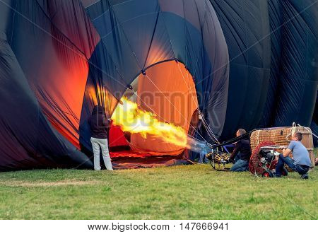 Ferrara Italy 09-17-2016: three hot air balloon pilots inflating hot air baloon with the burner and the fan