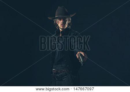 Vintage Cowboy Shooting With Gun. Young Man. Studio Shot Against Dark Wall.