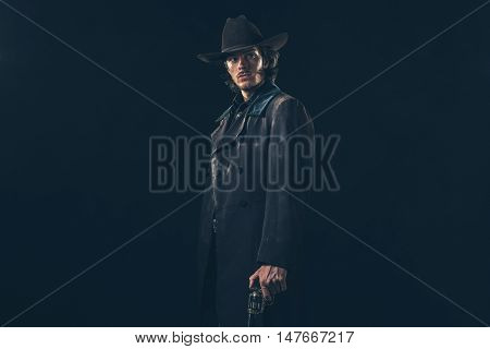 Menacing Vintage 1900 Cowboy Standing With Revolver. Studio Shot Against Dark Background.