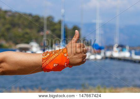 man's hand with raised thumb with orange bandana against the backdrop of marina Marmaris