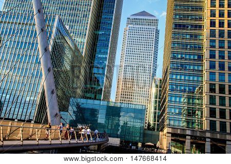London UK - August 29 2016 - People walking on the South Quay footbridge in Canary Wharf with One Canada Square in the background