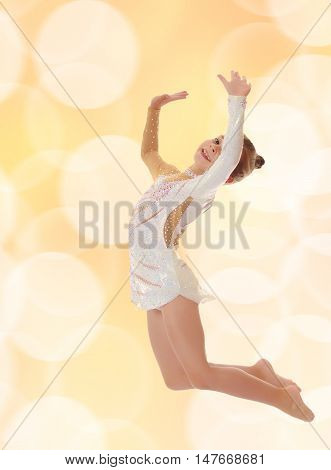 Beautiful little girl gymnast dressed in sports swimsuit, jumps high.On blurred brown background with white Christmas snowflakes.