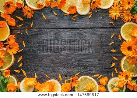 Frame of calendula flower heads and orange slices on the dark wood surface