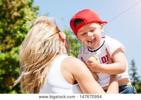 Mother throws son to the sky playing together outdoors in park laughing fells fun and happy