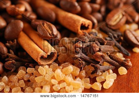 Coffee beans, cinnamon, sugar & clove. Close up.