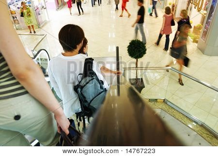People in escalators at the mall. No brand names or recognizable faces.