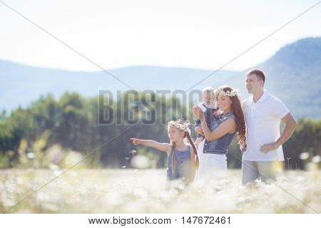 Happy family of four,mother,father,older sister and little brother spend time together in the highlands on a field of blooming white daisies in summer in the fresh air,mother and daughter wearing wreaths of flowers-white daisies