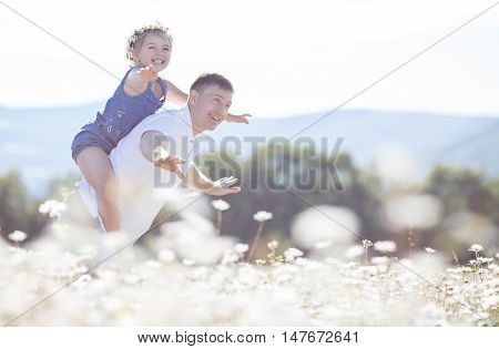 Cheerful family of two persons,father and little daughter spend time together in the highlands on a field of blooming white daisies in summer in the fresh air,a girl dressed in blue overalls and wears a wreath of wild flowers-white daisies