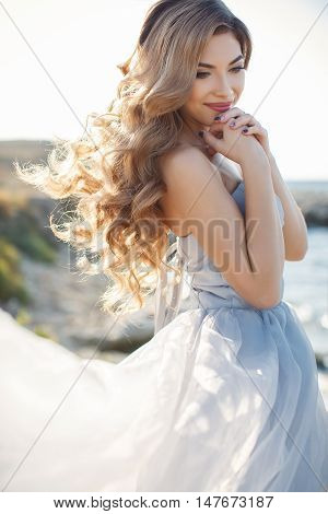 Beautiful young bride in long white wedding dress,off-shoulder beautiful long curly blonde hair,bride posing alone, standing on the rocky shore against the clear blue sky and ocean in summer time in fresh air