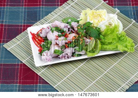 Spicy and sour mixed herb salad with squid wrap minced pork on bamboo. Side view.
