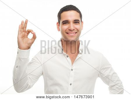 happy smiling young man with his an OK sign isolated against white studio background
