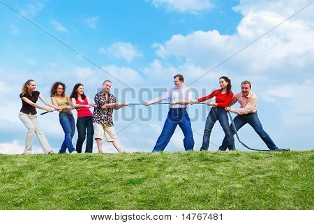 Group of happy people pulling the rope