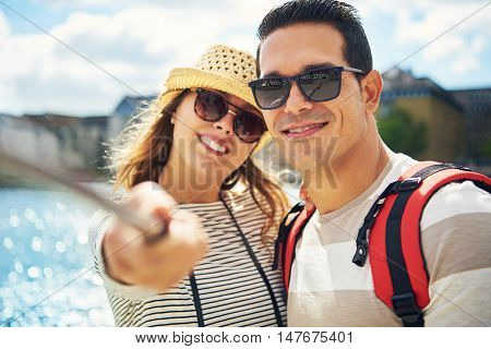Attractive happy friendly young couple or tourists standing smiling broadly as they pose together for a selfie at the seaside close up head and shoulders