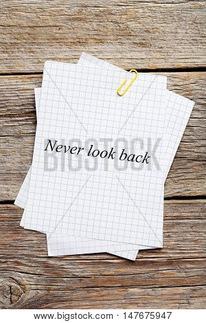 Sheet of paper on grey wooden background, never look back