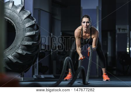 poster of Concept: power strength healthy lifestyle sport. Powerful attractive muscular woman fitness trainer do battle workout with ropes at the gym