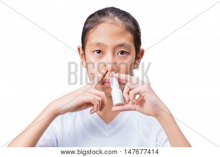 Teenage asian girl using nasal spray with one hand holding the spray bottle to her nose's left side and an index finger from the other hand pressing on her nose's right side to block the air flow on white background