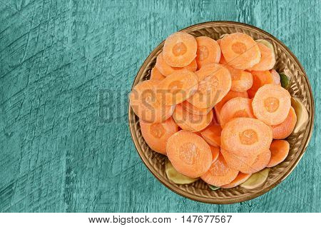 Sliced carrots in a bowl on wooden background. Tinted in blue-green color.