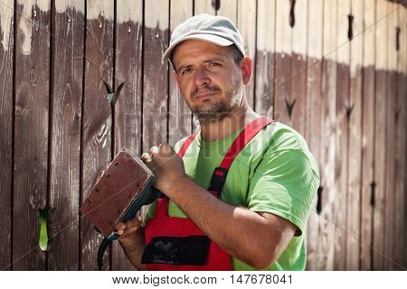 Worker about to scrape away the old paint from a wooden fence - standing with a vibrating sander