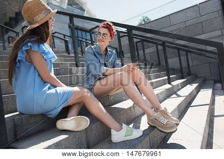 two young women sitting on the stairs and talking