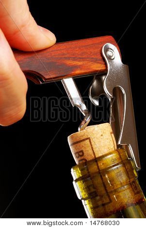 Opening a wine bottle with corkscrew, isolated on black