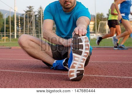 Runner making stretching on the athletic race  track