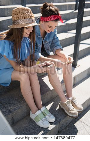 female students holding their phones and smiling outdoors