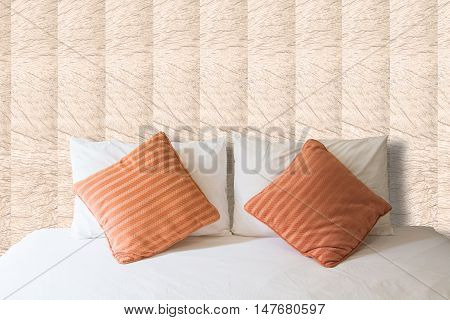white pillow and orange pillow on bed and with blanket in vintage bedroom