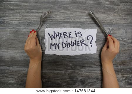 Where is my dinner? Fork in the left hand and knife in the right hand on the gray wooden textural background