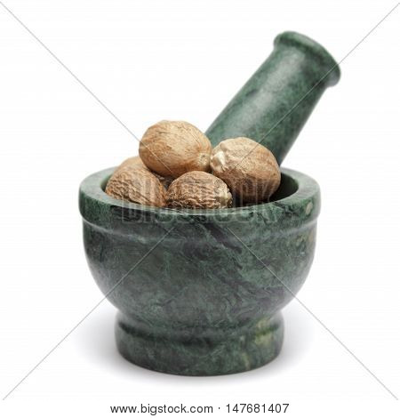 Organic Nutmeg Seed or Jaiphal (Myristica fragrans) on marble pestle. Isolated on white background.
