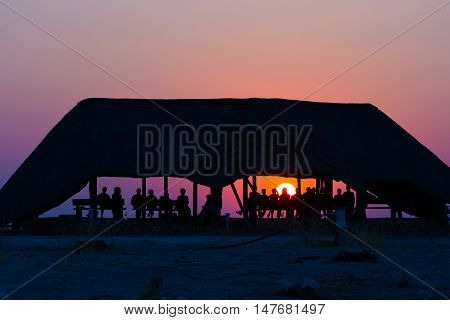 Group Of Tourists Watching Colorful Sunset Under Shelter. Tourist Resort In Africa. Backlight, Silho