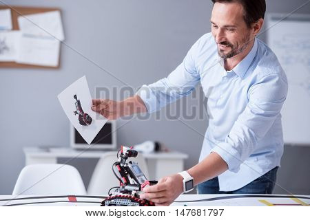 Mission accomplished. Middle-aged attractive male finished his work on a new invention of robot