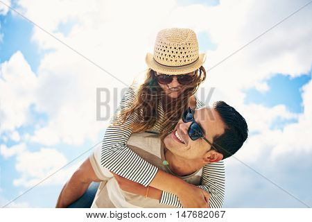 Handsome young man with his loving wife or girlfriend having fun relaxing on summer vacation piggy back riding against a sunny cloudy blue sky