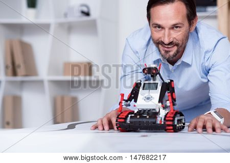 Well done. Energetic good-looking man presenting a robot he created